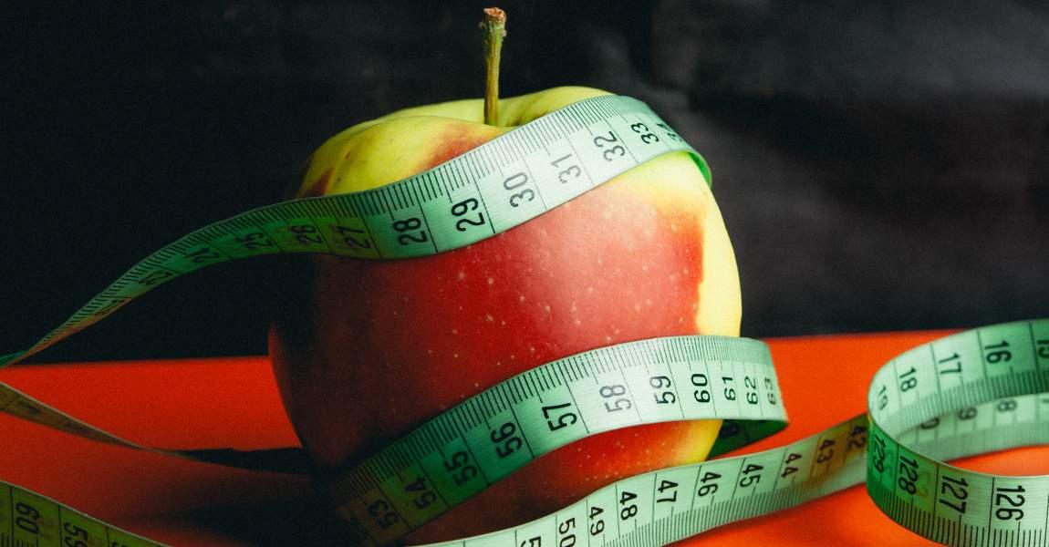 Яблоко, портновский сантиметр, красный стол, фото